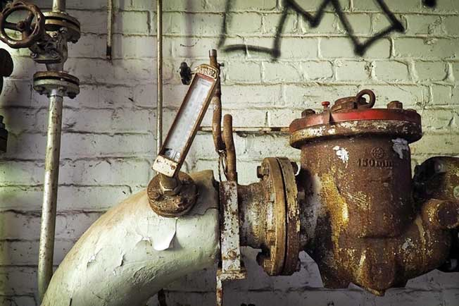 Rusted big pipe with a thermometer in front of white wall.