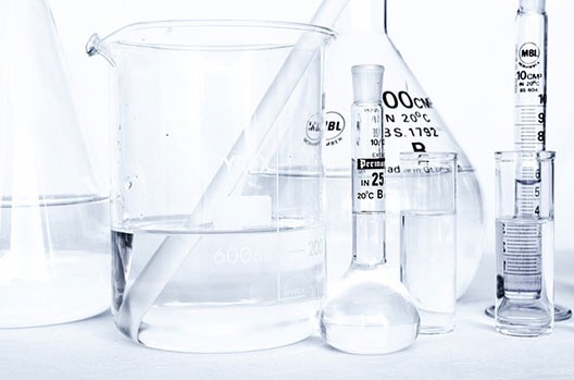 Several test glasses of different sizes filled with hydrochloric acid.