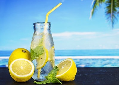 Bottle with straw filled with lemon. Half lemons lay around the bottle. ocean and blue sky in the background.