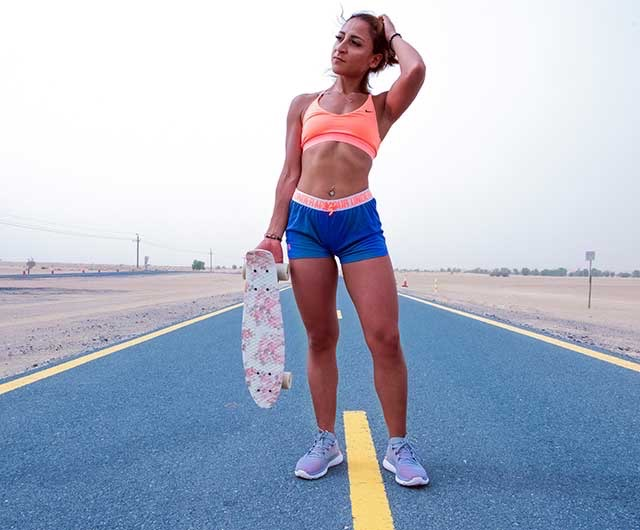 Woman wearing special workout clothing, staying on the highway holding skateboard in right hand.