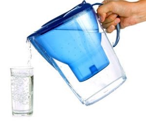 A plastic pitcher with a blue filtration unit puts water into a glass.