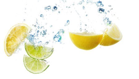 Lemon and lime slice falling into water