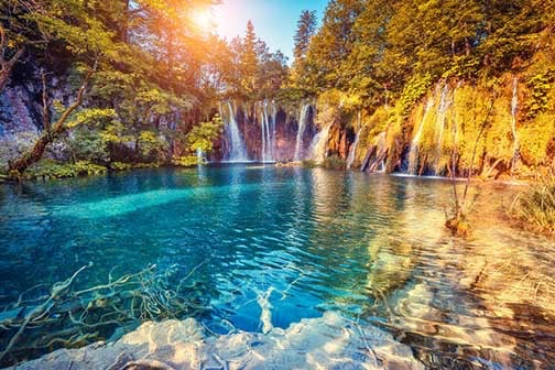 Waterfall with sun in the background. Turquoise water and stones in front.