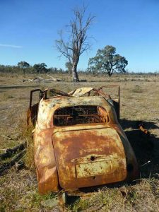 A rusted car without wheels and windows on the ground, blue sky. Some trees in the background.