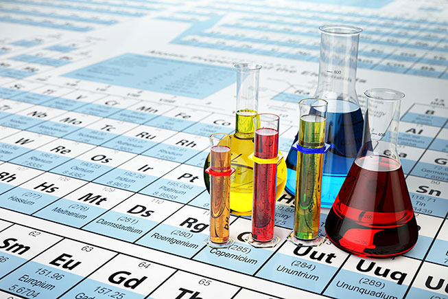 Different test tubes with hydrochloric-acid inside. Blue, red and yellow liquid. Placed on a periodic table.