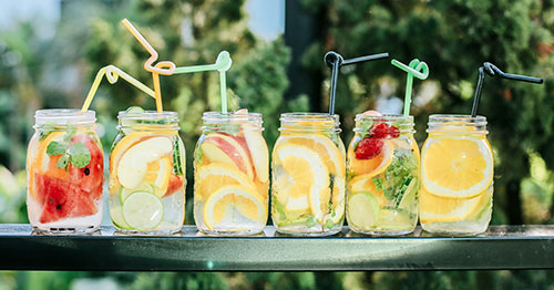 Six jars filled with alkaline fruits and veggies with straws placed on a table in the sun.